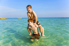 Brothers are enjoying the clear warm water in the ocean and play Stock Images