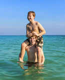 Brothers are enjoying the clear warm water in the ocean and play Royalty Free Stock Photos