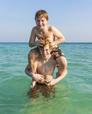 Brothers are enjoying the clear warm water in the ocean and play Royalty Free Stock Image