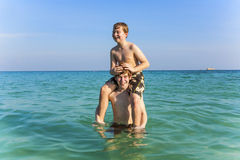 Brothers are enjoying the clear warm water in the ocean and play Stock Photos