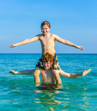 Brothers enjoying the clear warm water and play piggyback Stock Photos