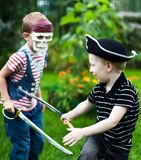 Brothers fighting. Two brothers wearing pirate costumes and skull mask fighting Royalty Free Stock Photo