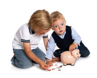 Brothers filling their piggy bank Royalty Free Stock Photo