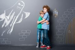 Brothers are frightened by ghost. Childhood fears. Two boys are holding each other standing in an old castle, depicted with chalk on neutral background royalty free stock photos