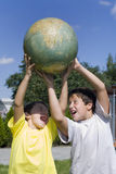 Brothers and globe. On lawn in courtyard of the building Royalty Free Stock Photo