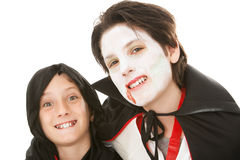 Brothers on Halloween. Two brothers dressed in their Halloween costumes. One is a goblin and the other is a vampire. White background royalty free stock image
