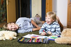 Brothers having fun. Brothers lying on the floor and draw Royalty Free Stock Photo