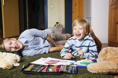 Brothers having fun. Brothers lying on the floor and draw Stock Photo