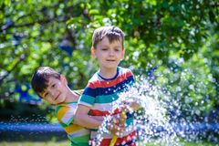 Brothers having fun splash each other with water in the village stock photography