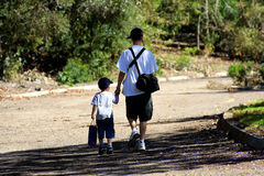 Brothers heading home. Big and little two brothers walking away holding hands at end of the day closeness and love they are buddies - Brothers Heading Home Royalty Free Stock Image