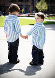 Brothers Holding Hands. Two identically dressed brothers holding hands in a park. High-contrast style Royalty Free Stock Photos
