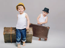 Brothers holding their heavy luggages Royalty Free Stock Images