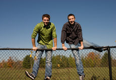 Brothers Hoping a fence Stock Images