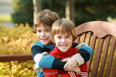 Brothers Hugging. Sitting on a Park Bench royalty free stock photography