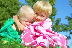 Brothers Hugging in Beach Towels. Two brothers, a baby and a youg child, hugging each other outside in a beach towel on a sunny summer day royalty free stock image