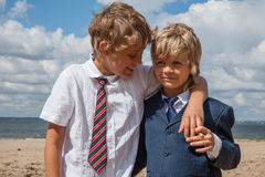 Brothers hugging on the beach. Two boys wearing business suits - best friends hugging on the beach royalty free stock photos