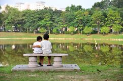 Brothers hugging each other facing a lake. Family and love concept royalty free stock photo