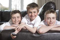 Brothers hugging and playing on the sofa. Three brothers hugging and playing on the sofa royalty free stock images