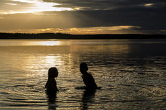 Brothers In The Water Of A Lake At Sunset Stock Photo