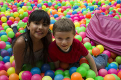Brothers lays on the big heap of multicolored small balls. Royalty Free Stock Images