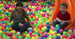 Brothers lays on the big heap of multicolored small balls. Royalty Free Stock Image