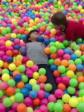 Brothers lays on the big heap of multicolored small balls. Stock Photography