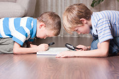Brothers are looking through a magnifying glass. Royalty Free Stock Image