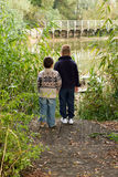 Brothers looking out across a pond in Autumn Stock Image