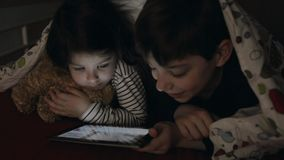 Brothers looking at the tablet in the dark stock video footage