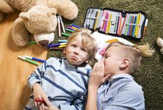 Brothers having fun. Brothers lying on the floor and draw Royalty Free Stock Images