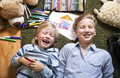 Brothers having fun. Brothers lying on the floor and draw Royalty Free Stock Photos