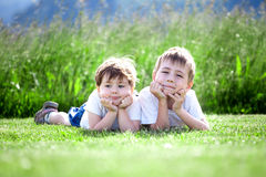 Brothers lying on grass. Two cute preschool brothers lying on green grass with field in background stock images