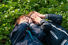 Brothers lying on the meadow. Four year old twin boys  lie on the blooming grass Royalty Free Stock Images