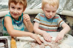 Brothers making gingerbread cookies. Two young brothers making christmas gingerbread cookies Royalty Free Stock Photo