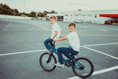 Brothers making tricks riding on one bike together. Active brothers making tricks riding on one bike together, elder brother riding bike, younger brother sitting royalty free stock images