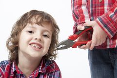 Brothers  with missing tooth and combination plier. Portrait of cute brothers  with missing tooth and combination pliers Royalty Free Stock Photo