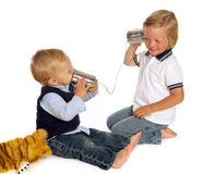 Brothers on the phone. Two little brothers talking on the phone using two cans and a piece of rope Royalty Free Stock Photography