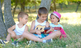 Brothers play guitar and sing in garden in summer. Brothers play guitar and sing in garden Stock Photo