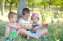 Brothers play guitar and sing in garden in summer. Brothers play guitar and sing in garden Royalty Free Stock Photo