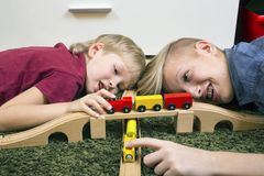 Brothers play with wooden train, build toy railroad at home or d. Children play with wooden toy, build toy railroad at home or daycare. Toddler boy play with Royalty Free Stock Photos