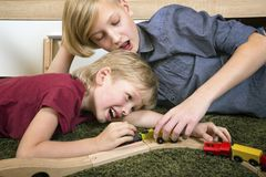 Brothers play with wooden train, build toy railroad at home or d stock image