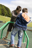 Brothers on playground, climbing a roped frame Royalty Free Stock Photo