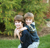 Brothers Playing. Around Giving Piggy Back Rides Stock Photo