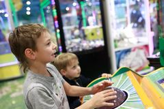 Brothers playing arcade game. In amusement park stock images