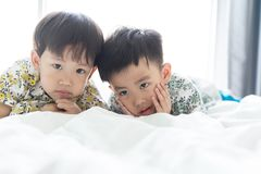 Brothers are playing the morning on the bed stock photography