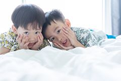 Brothers are playing the morning on the bed royalty free stock photo