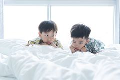 Brothers are playing the morning on the bed stock images