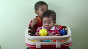 Brothers playing with multicolored balls.