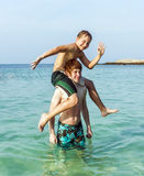 Brothers playing piggyback in the ocean Stock Image