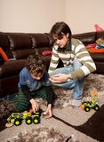 Brothers playing with plastic trucks Stock Photo